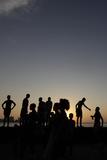 People Stand Along Havana's Seafront Boulevard El Malecon During Sunset Photographic Print by Enrique de la Osa