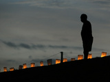 A New Orleans Resident Stands During a Candlelight Ceremony Photographic Print by Carlos Barria