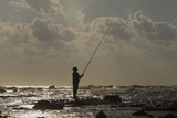 A Man Fishes Near the Seaport in Benghazi Photographic Print by Esam Al-Fetori