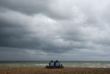 A Couple Sit on an Almost Deserted Beach at Brighton in South East England Photographic Print by Toby Melville