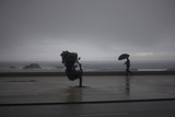 A Man with an Umbrella Walks in Front of the Beach During a Storm in Vila Do Conde Photographic Print by Miguel Vidal