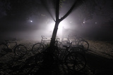 A Security Guard Wears a Shawl Amid Dense Fog Next to Parked Bicycles Outside a Shopping Mall Photographic Print by Parivartan Sharma