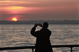 A Tourist Takes a Photo at Sunset in New York's Battery Park Photographic Print by Brendan McDermid