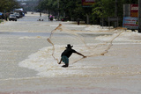A Man Casts a Fishing Net into Floodwaters Photographic Print by Sukree Sukplang