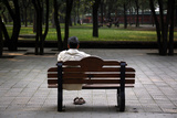 A Man Stretches as He Sits on a Bench at Ritan Park Located in Central Beijing Photographic Print by David Gray
