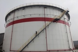 A Worker Walks Down Stairs of an Oil Tank at a Refinery in Wuhan, Hubei Province Photographic Print by Darley Shen