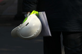 A Construction Worker Carries a Hard Hat in London Reproduction photographique par Luke MacGregor