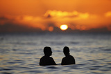 A Couple Watches the Sunset from the Waters Off Waikiki Beach During New Year's Eve in Honolulu Photographic Print by Jason Reed