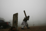 A Man Plays Cricket Amid Heavy Fog in New Delhi Fotografisk trykk av Adnan1 Abidi