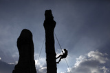 A Climber Reaches the Top of an Outdoor Climbing Wall in Berlin Photographic Print by Pawel Kopczynski