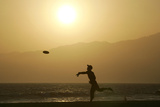 A Man Plays Frisbee on Venice Beach in Venice, California Photographic Print by Jonathan Alcorn