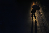 Commuter with an Umbrella Walks Through the Beam of a Bus Headlight During the Evening Rush Hour Photographic Print by TIM WIMBORNE