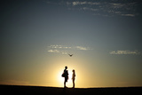 A Couple Stands on a Sand Bank as the Sun Sets in Venice, Los Angeles Photographic Print by Lucy Nicholson