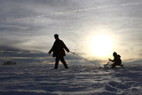 A Man Trails a Child on His Sledge During a Sunny Winter Day Near Kempten Photographic Print by Michaela Rehle