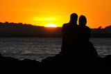 A Couple Watch the Sun Setting on a Beach Near Holyhead in Anglesey, North Wales Photographic Print by Toby Melville