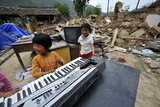 A Girl Plays on a Damaged Electronic Organ Photographic Print by China Daily