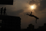 A Man Jumps into a Pool in Sanaa Photographic Print by Suhaib Salem
