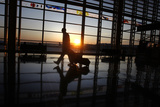 A Passenger Walks in Ronald Reagan Airport as the Sun Rises in Washington Photographic Print by Jason Reed