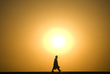 An Afghan Man Walks on the Street as the Sun Sets Photographic Print by Marko Djurica