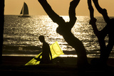 A Tourist Carries an Inflatable Raft While Walking Against the Setting Sun on Waikiki Beach Photographic Print by Larry Downing