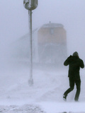 A Man Crosses a Railway Track During Heavy Snowfall Photographic Print by Eduard Korniyenko