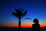 A Tourist Admires the Light after Sunset on the Beach Front of Olympia Riviera Resort Photographic Print by Yannis Behrakis