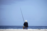 A Man Fishes at the Beach at Betty's Bay Near Kleinmond Photographic Print by Kai Pfaffenbach