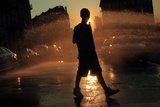 A Boy Walks Near Water Spraying from an Open Fire Hydrant Photographic Print by Eric Thayer