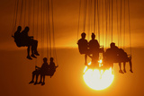 People Enjoy a Ride on a Circular Swing at Sunset in Athens Photographic Print by Yannis Behrakis