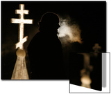 A Man Is Silhouetted by a Cross as People Prepare to Dip Posters by Sergei Karpukhin