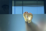 A Pair of Feet are Pressed Against Frosted Glass on a Balcony in Brighton Photographic Print by Luke MacGregor