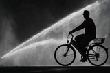 A Cyclist Rides His Bike Past the Spray of a Sprinkler in a Public Garden in Zurich Photographic Print by Christian Hartmann