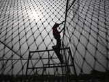 A Worker Fixes the Net onto a Cage Photographic Print by Sukree Sukplang