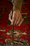 Worker Repairs Old Iranian Carpet at Tehran's Grand Bazaar Photographic Print by Morteza Nikoubazl