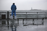 A Man Watches the Rising Tides in Battery Park as Hurricane Sandy Makes its Approach in New York Photographic Print by Andrew Kelly