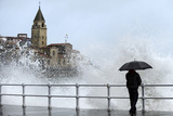 A Man Looks at Waves Crashing Against the Seawall in the Northern Spanish City of Gijon Photographic Print by Eloy Alonso