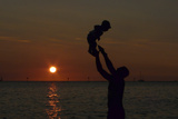 A Man Tosses His One-Year-Old Son into the Air as the Sun Sets over Waikiki Beach in Honolulu Reproduction photographique par Jason Reed
