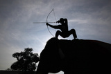 A Mahout Demonstrates His Archery Skills During a Regular Training Exercise with His Elephant Reproduction photographique par Sukree Sukplang