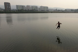 A Man Jumps into the Waters of the Yenisei River in Krasnoyarsk Photographic Print by Ilya Naymushin