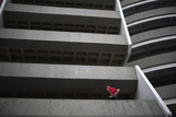 A Man Sits on the Parapet on the First Floor of a Public Carpark in Downtown Guatemala City Photographic Print by Jorge Lopez