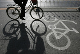 A Cyclist Rides Along a Bicycle Lane in Beijing Photographic Print by Claro Cortes