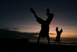 East Timorese Child Somersault as the Sun Sets at a Beach in Dili Photographic Print by Beawiharta Beawiharta