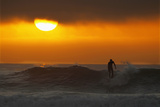 A Surfer Rides His Last Wave into Shore as the Sun Sets into an Incoming Layer of Fog in Cardiff Photographic Print by Mike Blake