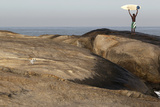 A Man Holds Up His Surfboard During a Winter Day Atop of a Rock Near Arpoador Beach Photographic Print by Sergio Moraes