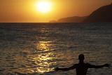 A Brazilian Man Is Seen During Sunset on Arpoador Beach in Rio De Janeiro Photographic Print by Sergio Moraes