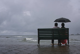 A Couple Rests on a Seaside Promenade During a Rain Shower in Kochi Photographic Print by Sivaram V