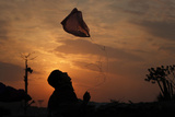 Boy Is Silhouetted Against Setting Sun While Playing with Plastic Bag Tied to Strings Photographic Print by Faisal Mahmood