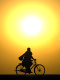 A Man Rides a Bicycle as the Sun Sets at Delaram District in Nimroz Province, Southern Afghanistan Photographic Print by Marko Djurica