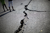 Children Walk Past a Crack Caused by the Earthquake in a Street in Port-Au-Prince Photographic Print by Carlos Barria