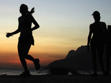 A Brazilian Woman Runs During Sunset Near Arpoador Beach in Rio De Janeiro Photographic Print by Sergio Moraes